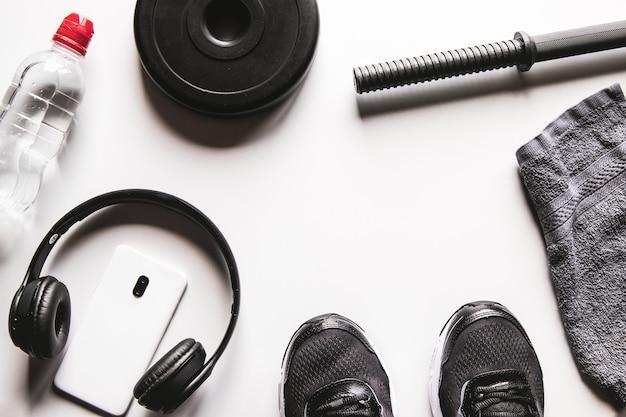 Asciugamano, scarpe da ginnastica, acqua e smartphone con le cuffie su un bianco Foto Premium