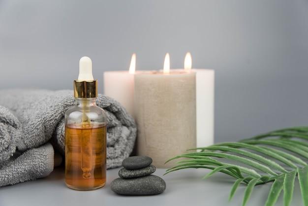 Asciugamano con candele aromatiche, bottiglia con oli essenziali biologici naturali Foto Premium