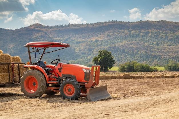 Trattore in campo agricolo con montagne e cielo blu Foto Premium