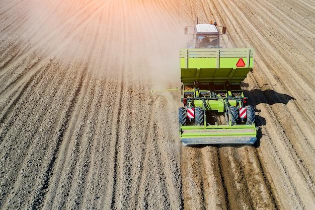 Trattore nel campo che pianta le patate nei campi agricoli fertili Foto Premium