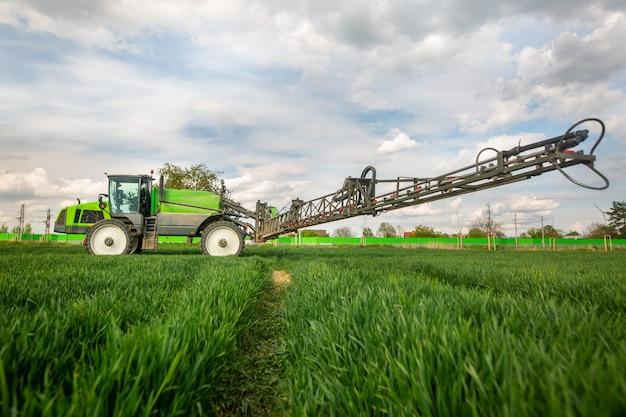 Trattore irrorazione di pesticidi, fertilizzazione sul campo vegetale con irroratore a primavera, concetto di fertilizzazione Foto Premium