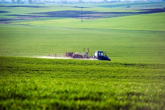Trattore che spruzza pesticidi sul campo con lo spruzzatore in estate Foto Premium