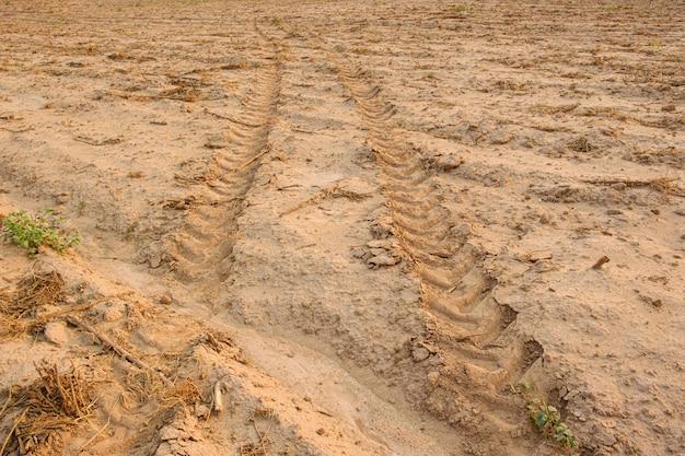 Tracce del trattore sul terreno. segni di ruota sul terreno. terriccio sciolto Foto Premium