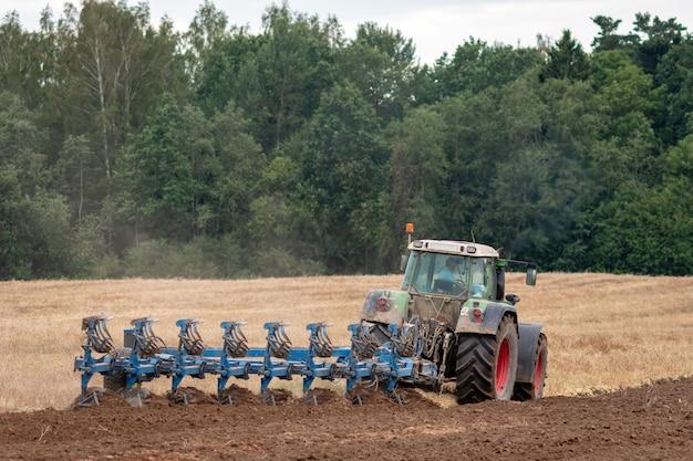 Un trattore con aratro tratta il terreno. Foto Premium