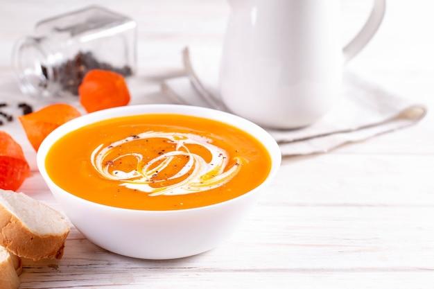 Piatti tradizionali autunnali e invernali, zuppa di zucca calda e piccante, panna e baguette appena sfornate su un tavolo bianco, copia dello spazio Foto Premium