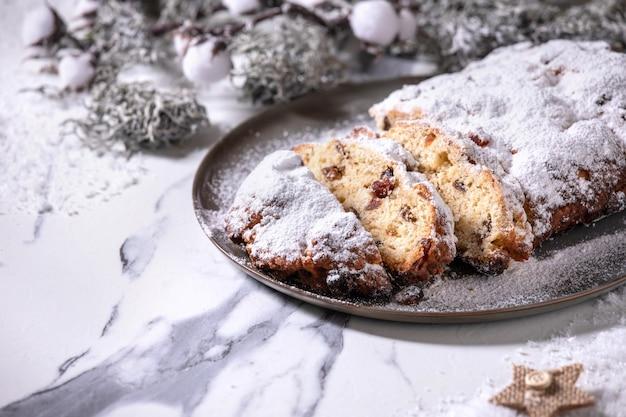 Natale tedesco casalingo tradizionale che cuoce il pane della torta di stollen sulla zolla con le decorazioni d'argento di natale sopra fondo di marmo bianco Foto Premium