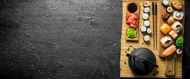 Sushi, maki e panini giapponesi tradizionali su un tovagliolo. su fondo rustico Foto Premium