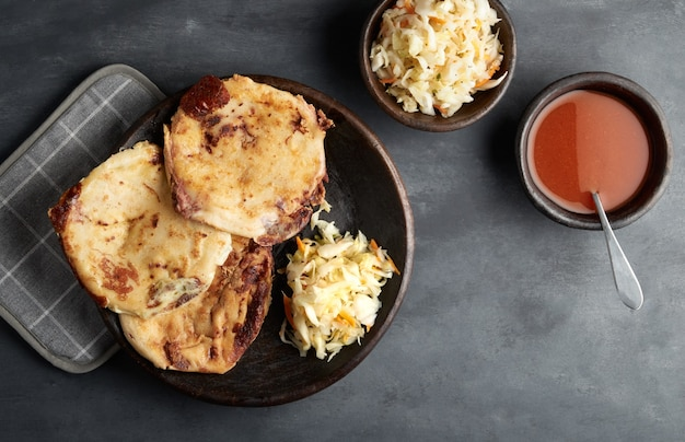 Tradizionale colazione e cena salvadoregna, tortillas di mais ripiene di maiale, formaggio e fagioli, cibo dell'america latina Foto Premium