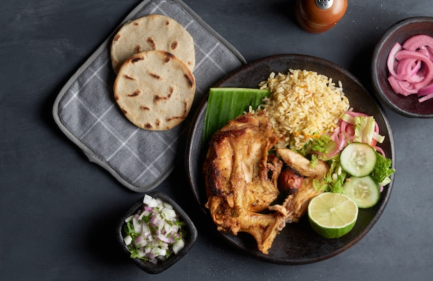 Gallina arrosto piatto tradizionale salvadoregno servito con tortillas di riso, limone, cipolla e mais, cibo dell'america latina Foto Premium