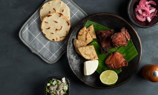 Spuntino di maiale salvadoriano tradizionale servito con tortillas di cipolla e mais, cibo dell'america latina Foto Premium