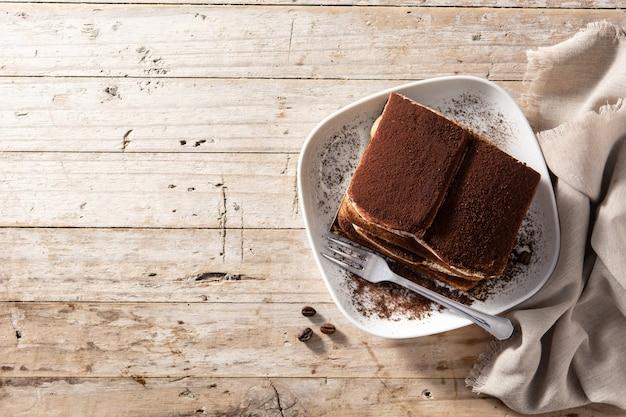 Torta tiramisù tradizionale sulla tavola di legno Foto Premium