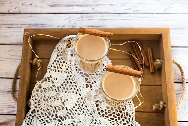 Zabaione invernale tradizionale in tazza di vetro con latte, rum e cannella, decorazioni natalizie. Foto Premium