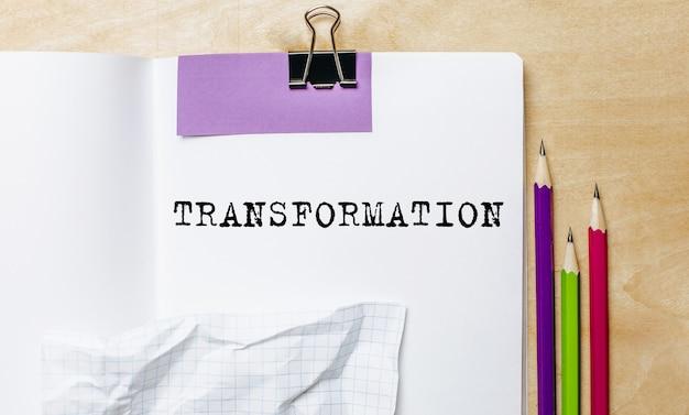 Testo di trasformazione scritto su un foglio con le matite sulla scrivania in ufficio Foto Premium