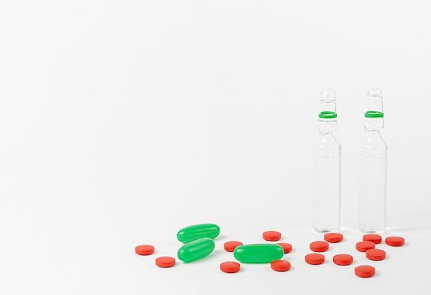 Bottiglie trasparenti di vaccino, pillole rosse e verdi sulla parete bianca. copia spazio Foto Premium