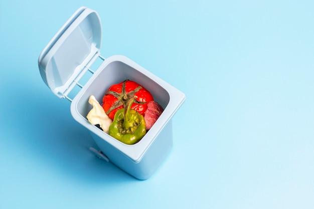 Pattumiera con spreco alimentare dentro sulla vista superiore del fondo blu, concetto di separazione dell'immondizia Foto Premium