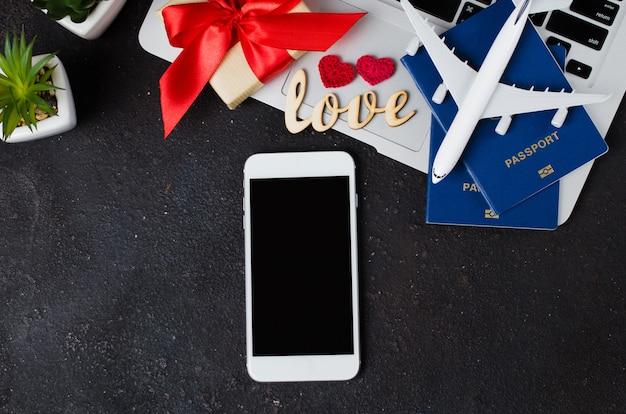 Concetto di prenotazione del viaggio. smartphone, modello di aeroplano, laptop, passaporti e confezione regalo su sfondo scuro. Foto Premium