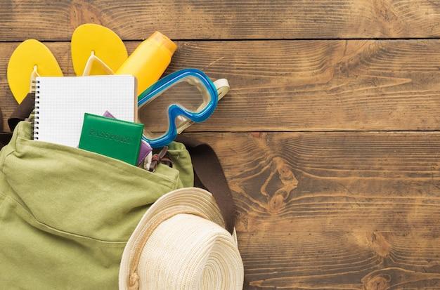 Concetto di pianificazione del viaggio. zaino piatto con accessori per notebook e viaggiatore in bianco sul tavolo di legno Foto Premium