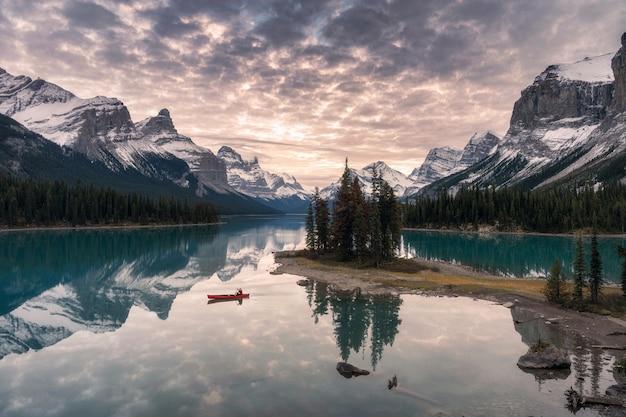 Canoa del viaggiatore con la riflessione della montagna rocciosa sul lago maligne all'isola di spirito nel parco nazionale di jasper Foto Premium