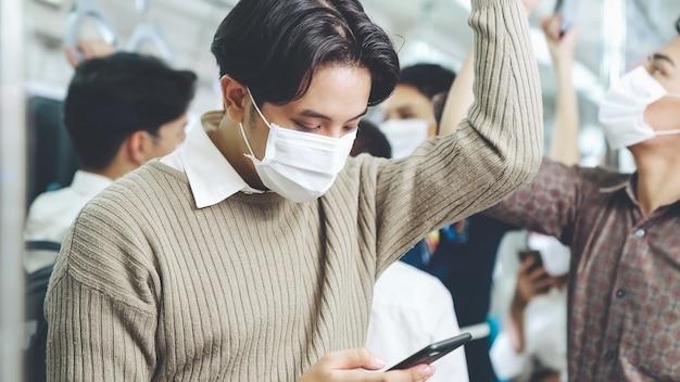Viaggiatore che indossa la maschera per il viso mentre si utilizza il telefono cellulare sul treno pubblico. malattia da coronavirus o epidemia di pandemia covid 19 e problema dello stile di vita della città urbana nel concetto di pendolarismo nelle ore di punta. Foto Premium