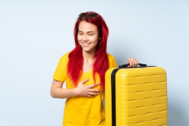 Donna del viaggiatore che giudica una valigia isolata sulla parete blu che sorride molto Foto Premium