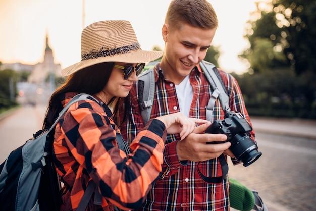 I viaggiatori con gli zaini guardano le foto scattate. escursioni estive. escursione all'avventura di una giovane coppia Foto Premium