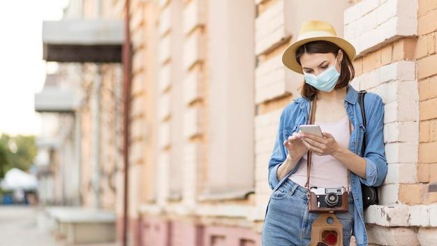 Viaggiatore con cappello e maschera viso navigando cellulare Foto Premium