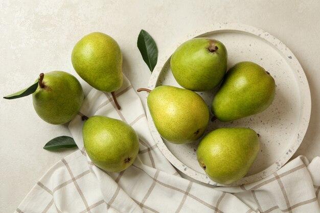 Vassoio con pere verdi e asciugatutto su bianco testurizzato Foto Premium