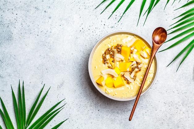 Ciotola frullato tropicale con mango, frutto della passione e cocco, sfondo chiaro. Foto Premium