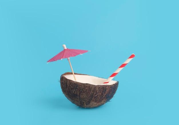 Estate tropicale e concetto minimo di vacanza. noce di cocco su uno sfondo blu con una cannuccia di cocktail. vacanza, viaggio, idea di spiaggia. Foto Premium
