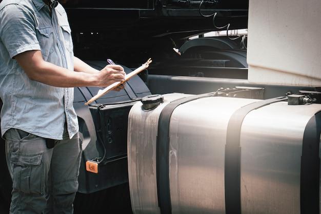 Un camionista che tiene la sicurezza degli appunti che controlla un grande serbatoio di carburante del camion dei semi. Foto Premium