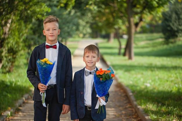 Due ragazzi adorabili con un bellissimo mazzo di fiori sulla natura Foto Premium