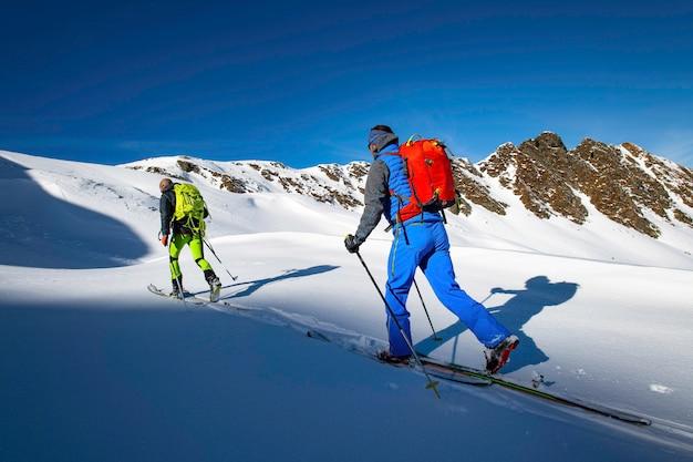 Due sciatori alpinisti durante un viaggio di sci alpinismo Foto Premium
