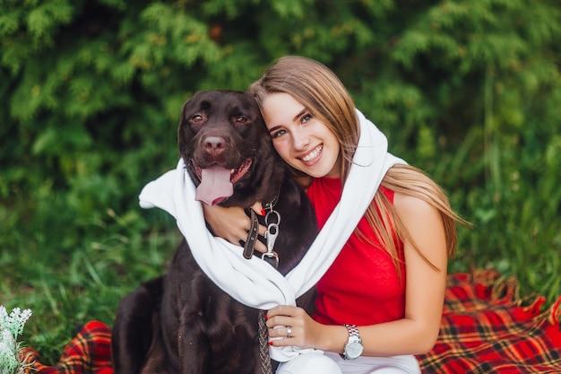 Due migliori amiche, una ragazza e il suo cane labrador seduto nel parco Foto Premium