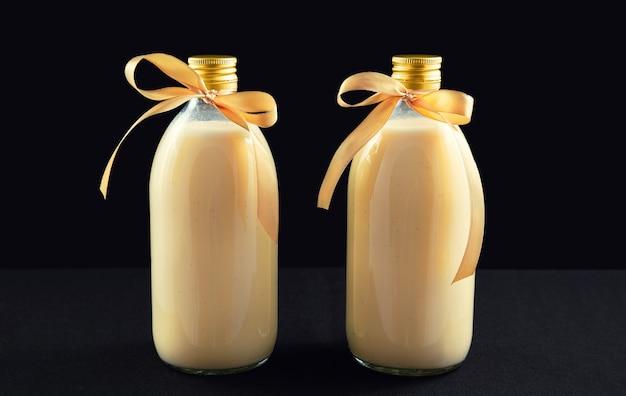 Due bottiglie di zabaione fatto in casa su sfondo scuro Foto Premium