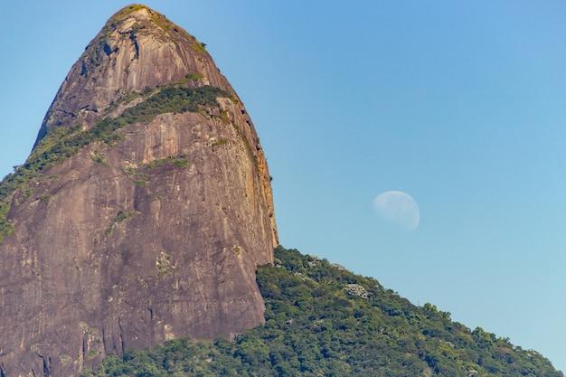 Collina dei due fratelli con l'impostazione della luna a rio de janeiro. Foto Premium