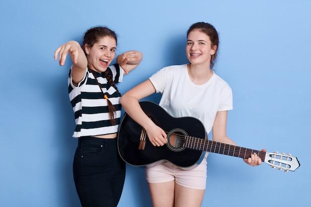 Due giovani ragazze divertenti castane ballano cantando e suonando la chitarra acustica mentre in piedi isolato sopra lo spazio blu Foto Premium