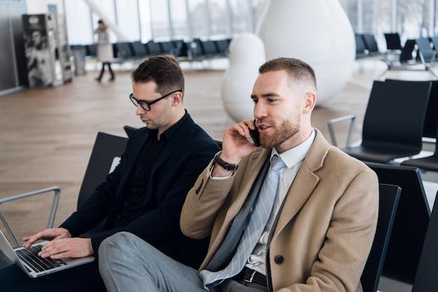 Due uomini d'affari che lavorano al computer portatile all'aeroporto Foto Premium