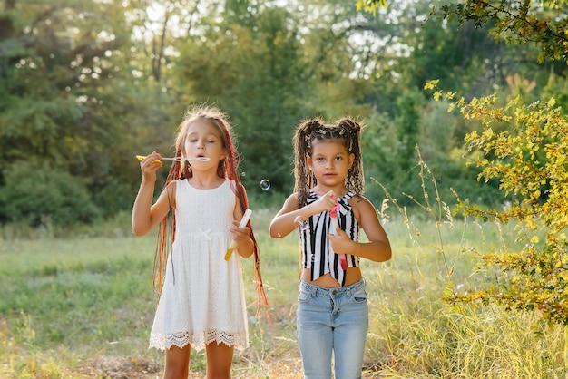 Due ragazze carine con le trecce stanno giocando nel parco facendo esplodere bolle di sapone. Foto Premium
