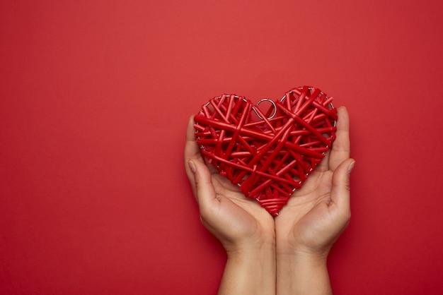 Due mani femminili che tengono un cuore di vimini rosso, concetto di amore, spazio della copia Foto Premium