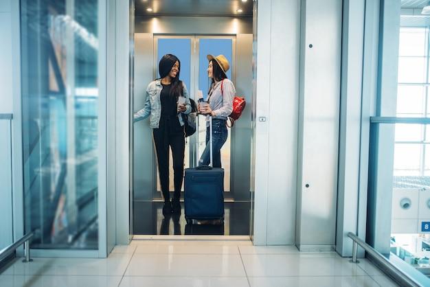 Due viaggiatori femminili con bagagli in ascensore dell'aeroporto. passeggeri con bagaglio in aerostazione Foto Premium