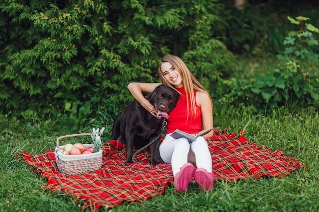 Due amici seduti sulla coperta intagliavano in giardino, una donna bionda e il suo cane Foto Premium