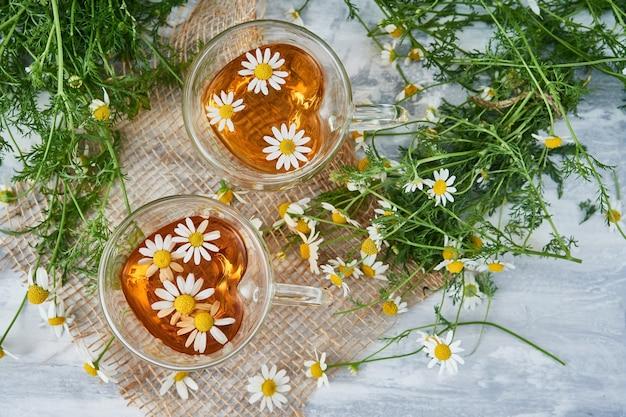 Due tazze di tè in vetro con camomilla, fiori di camomilla sparsi su un pezzo di tela Foto Premium