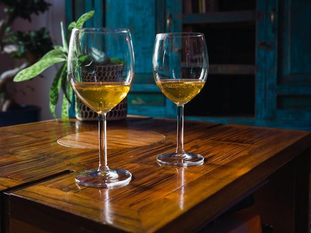 Due bicchieri di vino bianco in piedi sul tavolo Foto Premium