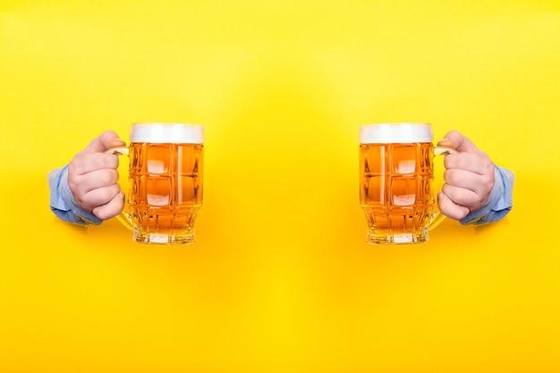 Due bicchieri di birra in mano su sfondo giallo Foto Premium