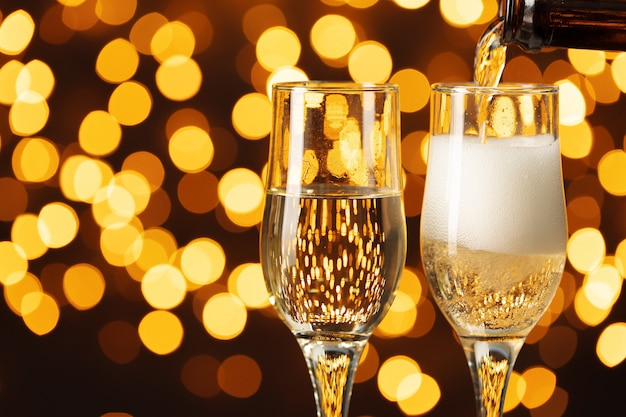 Due bicchieri di champagne contro il bokeh splendente sfondo luci Foto Premium
