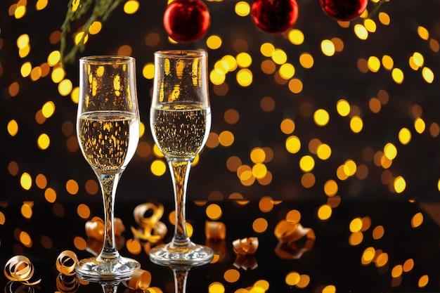 Due bicchieri di champagne e palline di natale su sfondo di luci bokeh splendente Foto Premium