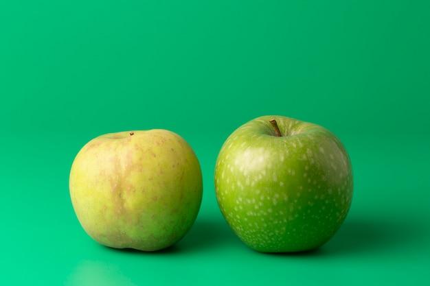 Due mele verdi su una verticale verde Foto Premium