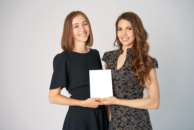 Due giovani donne felici che tengono un modello nei precedenti Foto Premium