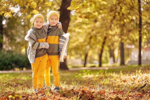 Due ragazzini in abiti identici nella soleggiata sera autunnale nel parco. due fratelli in età prescolare si divertono e giocano nel parco con fogliame dorato caduto. Foto Premium