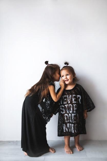Due bambine stanno chiacchierando, isolate su bianco, ragazze vestite con abiti di mamma a Foto Premium